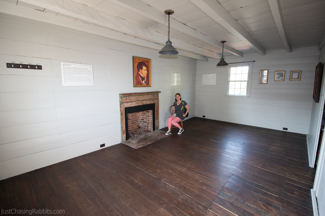 King's Tavern Haunted Room with white wooden walls, fireplace, and male portrait