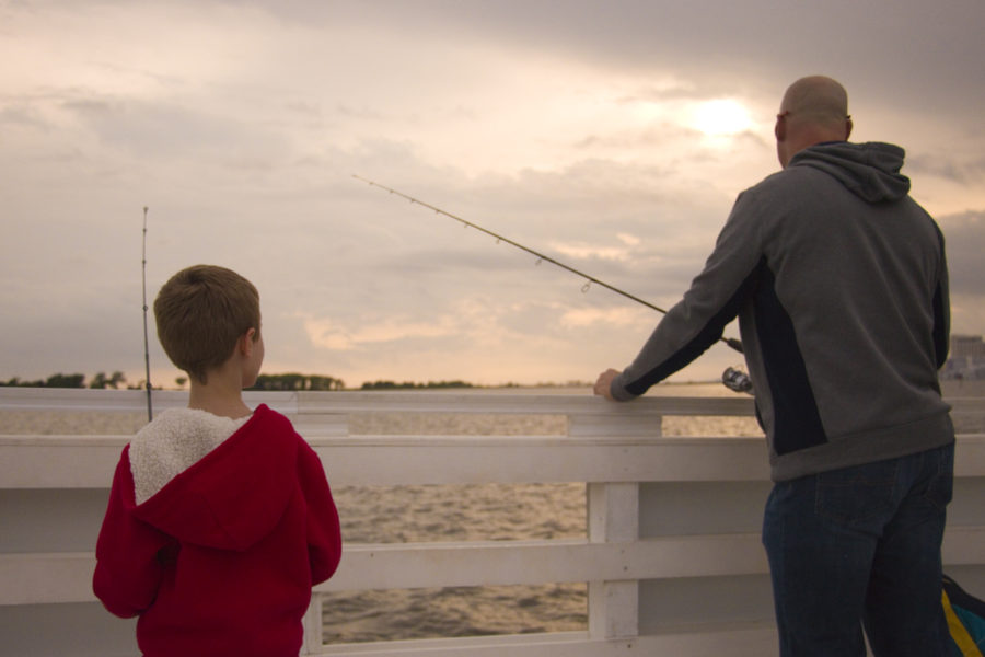 Father and son fishing while the sun sets