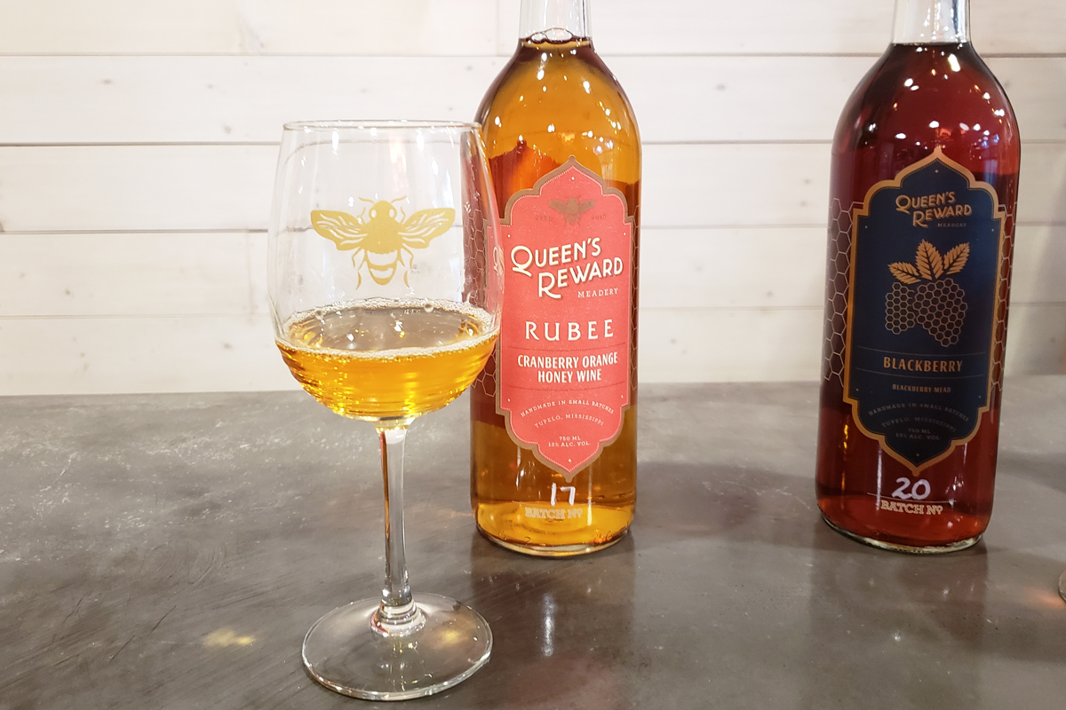 Glass of Queen's Reward mead with bottle