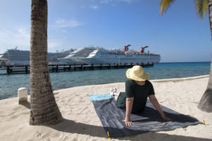 Jenni sitting on Cozy Beach Blanket with cruise ships in distance