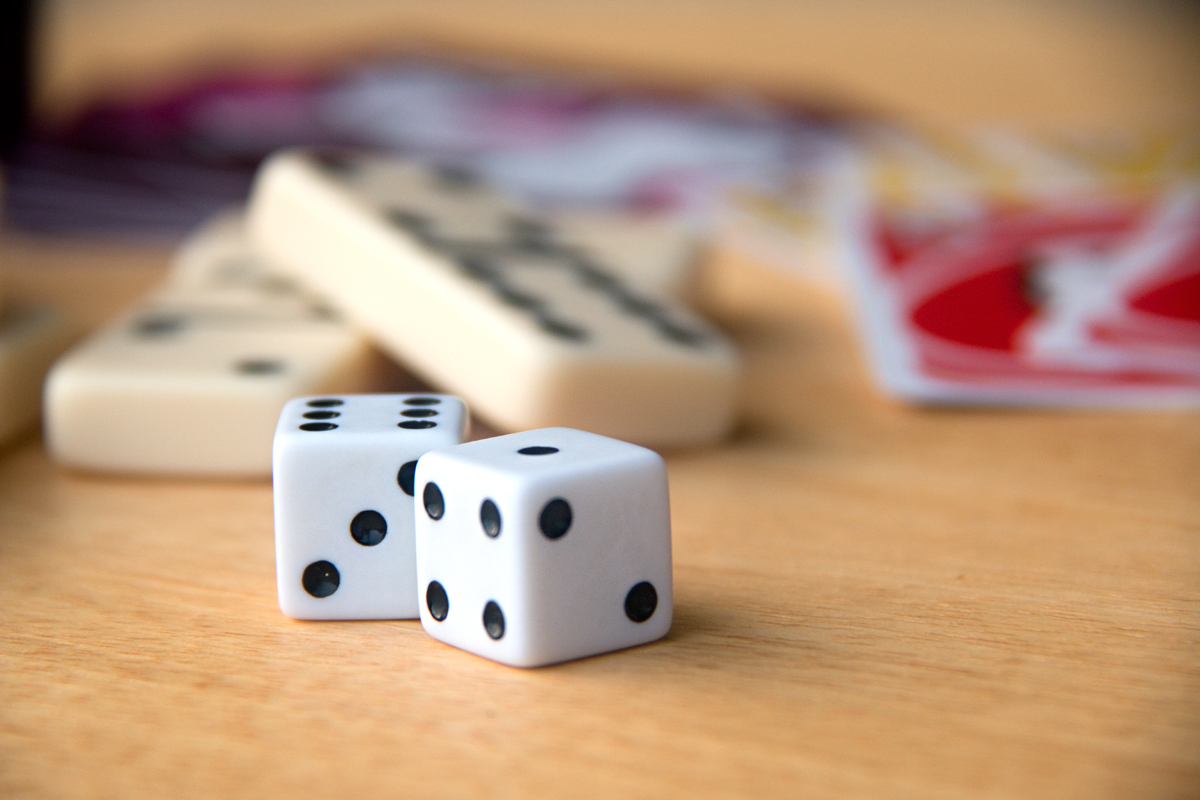 dice, dominoes, and cards on a wooden table