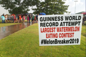 Largest watermelon eating contest sign and participants lined up in the rain