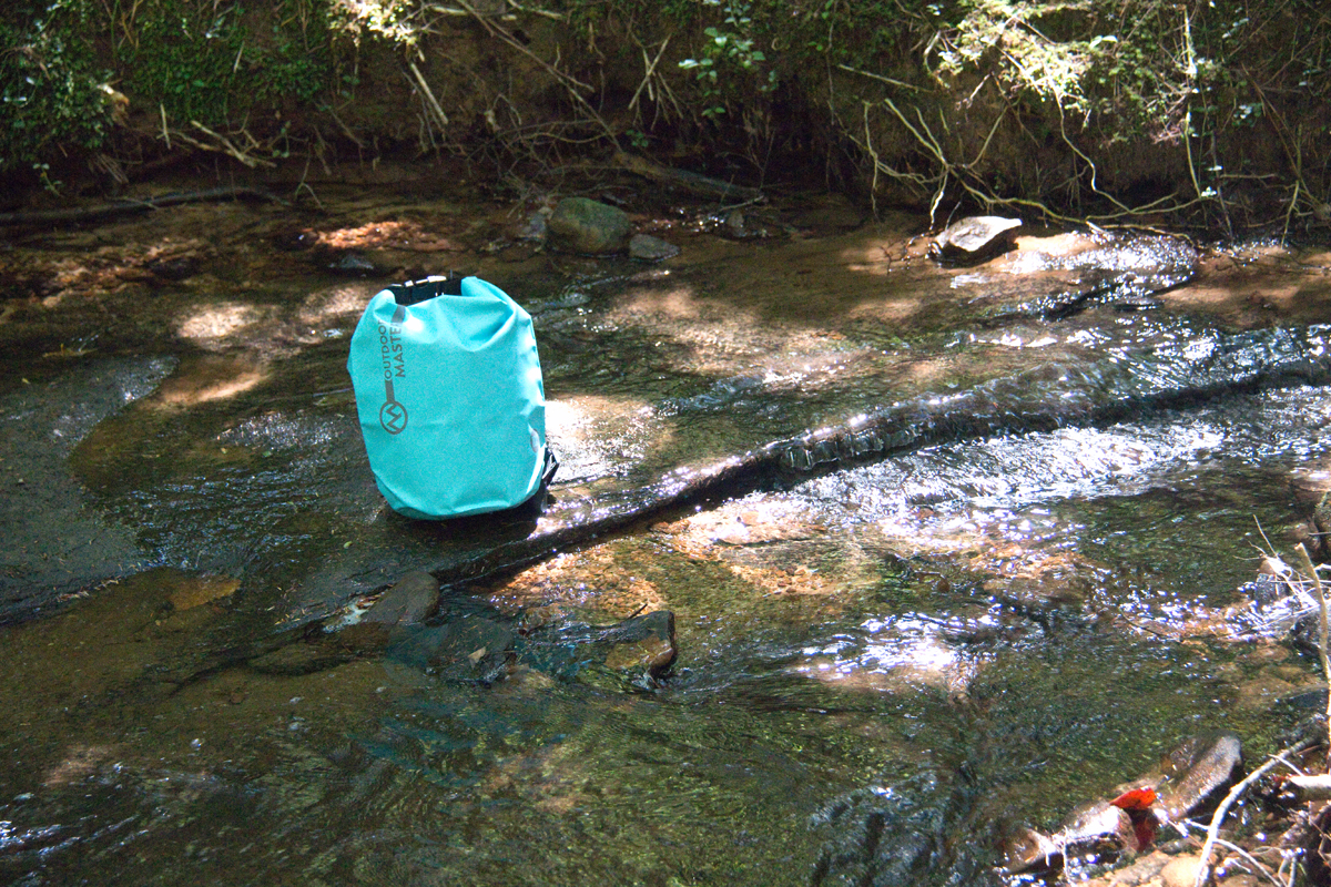 Outdoor Master dry bag sitting in a creek