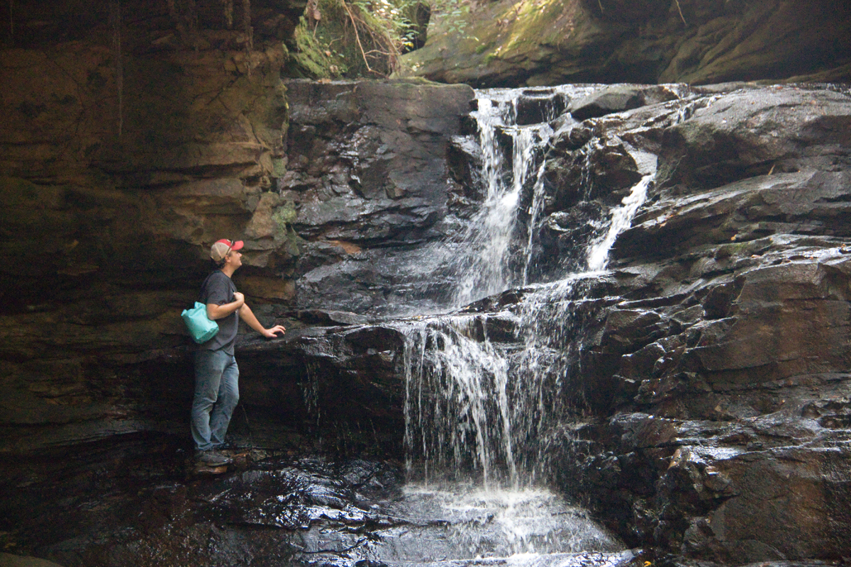 Mark holding Outdoor Master dry bag next to waterfall