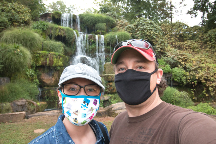 Mark and Jenni, wearing masks, in front of waterfall at Spring Park