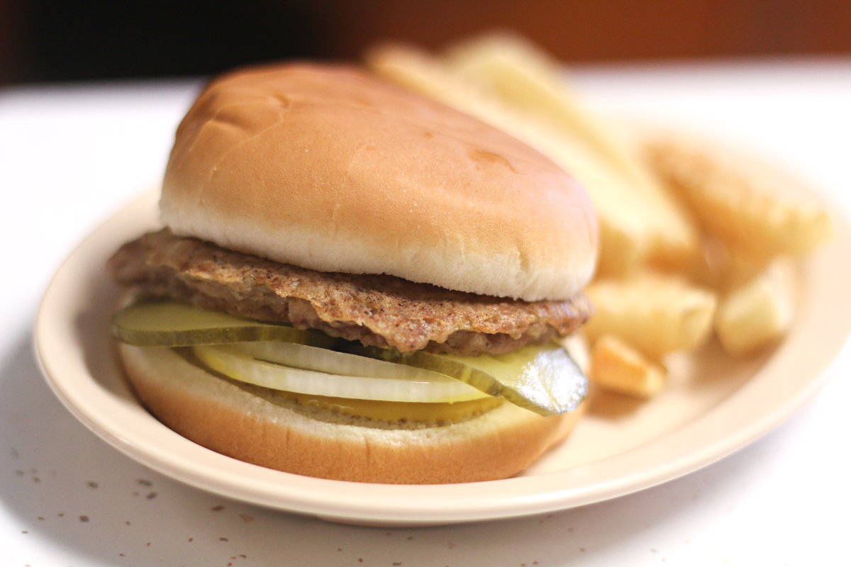 Doughburger and fries on a plate at Johnnie's Drive in