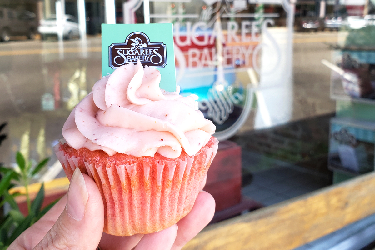 strawberry cupcake in front of Sugaree's bakery exterior