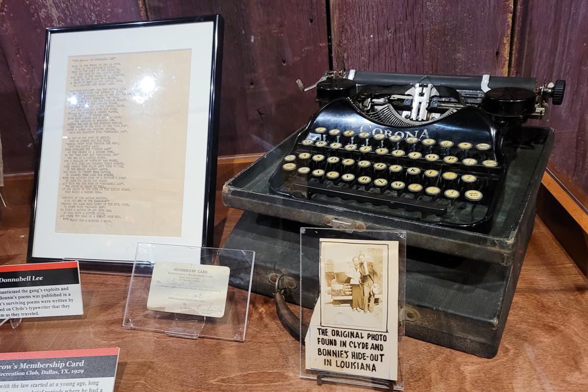 Personal items belonging to Bonnie and Clyde including photo, typewriter, membership card, and poem on display at Alcatraz East