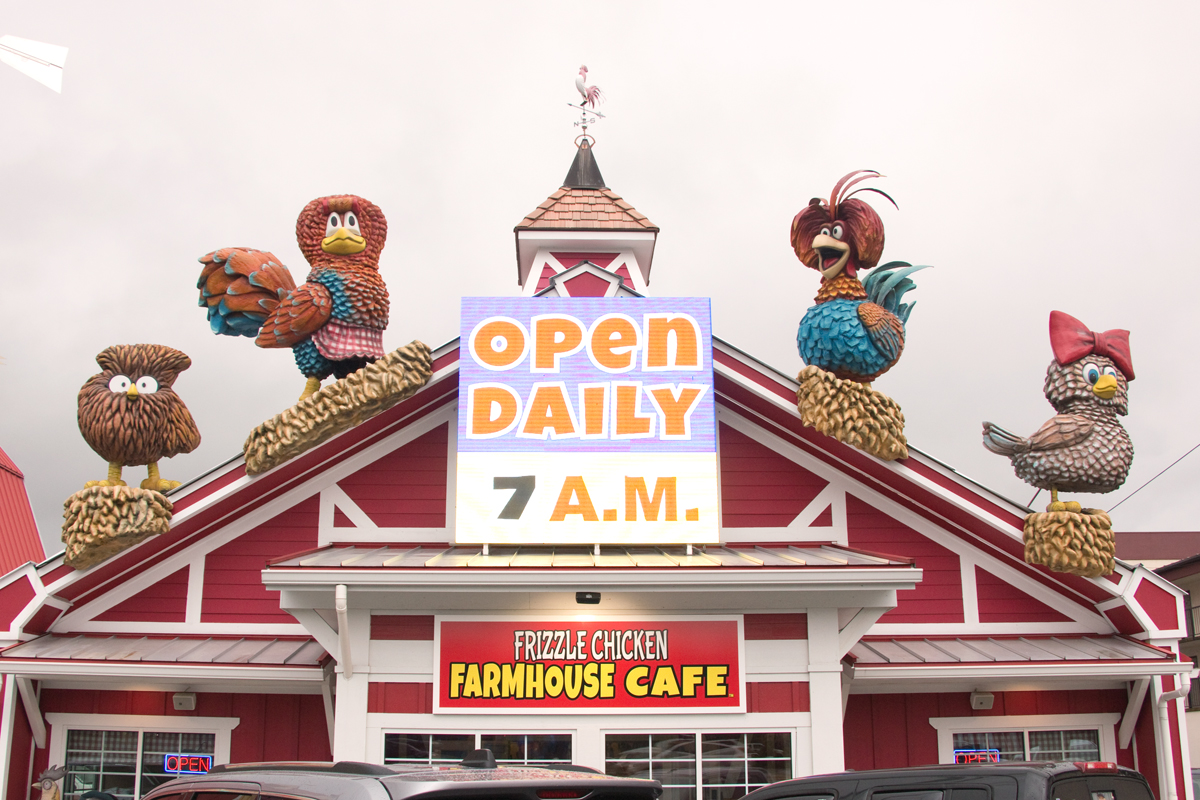 exterior of Frizzle Chicken Farmhouse Cafe with chicken statues on the roof