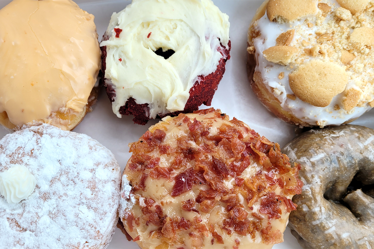selection of doughnuts from Mad Dog's Creamery and Donuts including banana pudding, blueberry, maple bacon, red velvet, Dreamcicle, and Dream Angel